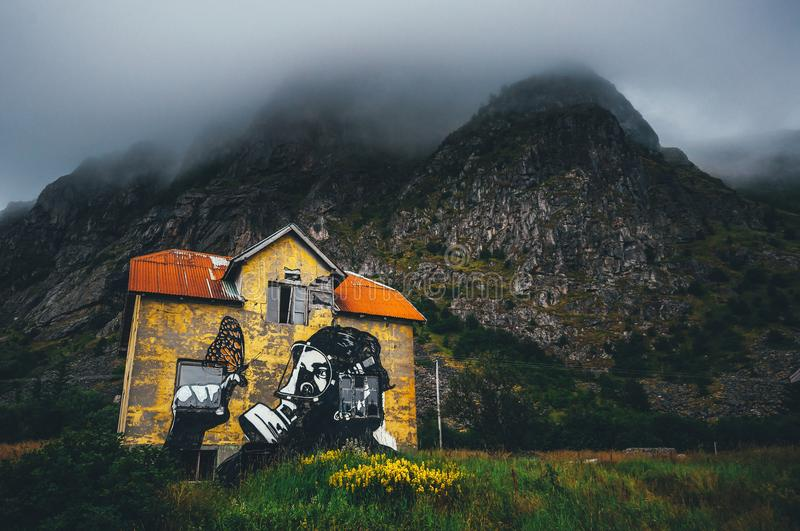 Hope in the decay. A Pøbel graffiti showing a man with a gas mask holding a butterfly. Street art painted on an old abandoned yellow painted house in Lofoten royalty free stock photography