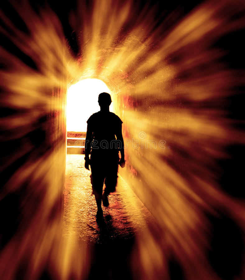 Hope at the End of the Tunnel. Person in long tunnel walking towards the end with light rays of hope