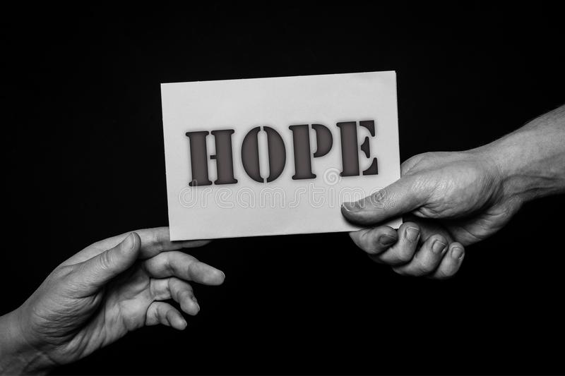 Hope, helping hands concept, offering care, love, hope and support. Helping hands, offering care, love, hope and support. a hand holding a card and giving to royalty free stock photos