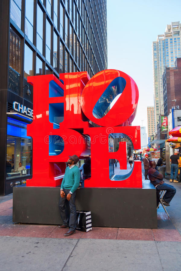 Hope sculpture from Robert Indiana in Midtown Manhattan, NYC. New York City, USA - October 07, 2015: Hope sculpture in Midtown Manhattan with unidentified people royalty free stock images