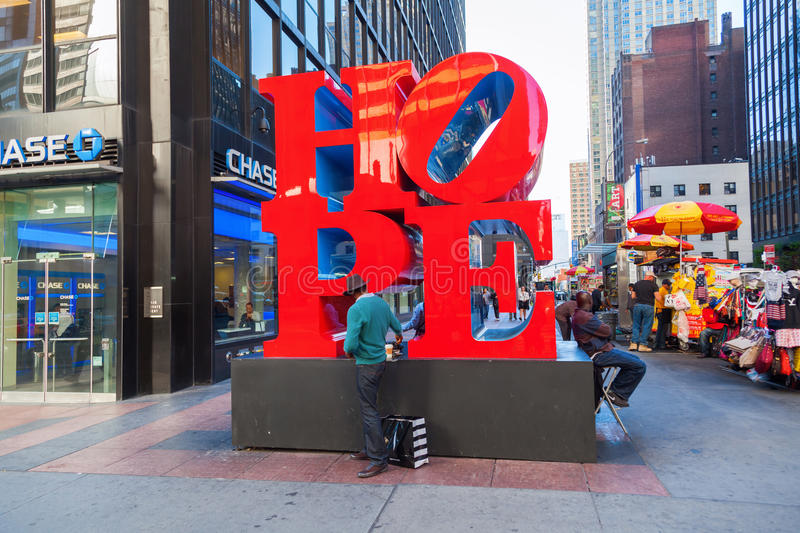 Hope sculpture from Robert Indiana in Midtown Manhattan, NYC. New York City, USA - October 07, 2015: Hope sculpture in Midtown Manhattan with unidentified people royalty free stock photography