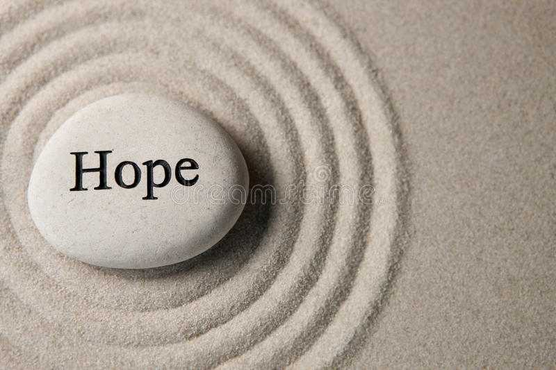 Hope stone. Inspirational stone surrounded by sand ripples. Zen concept