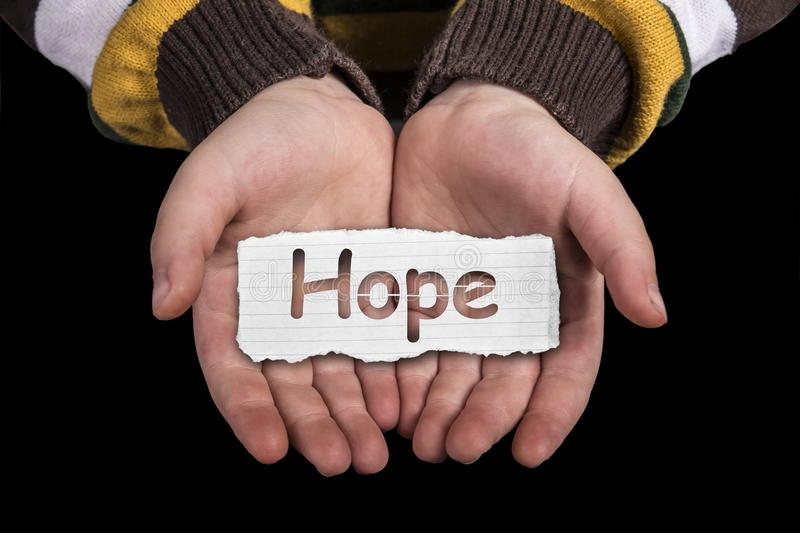 Hope text on hand. Hope text in line paper on child hand isolated on black background stock image