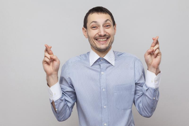 Hope to win. Portrait of funny handsome bristle businessman in classic blue shirt standing and looking at camera with hopeful eyes. And finger gesture. indoor stock photos