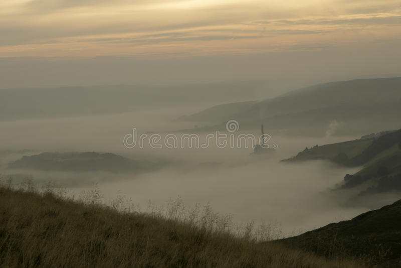 Hope valley through the mist. Early morning view of hope valley in mist, with the cement works poking through stock photography