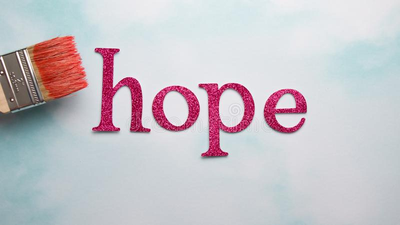 Hope word with pink sparkling paintbrush for breast cancer awareness month. Hope word with pink sparkling paintbrush for breast cancer survivors royalty free stock photography