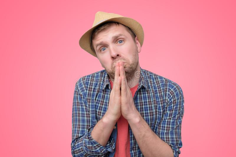 Hopeful man in summer hat join hands in prayer thanking asking for best royalty free stock image
