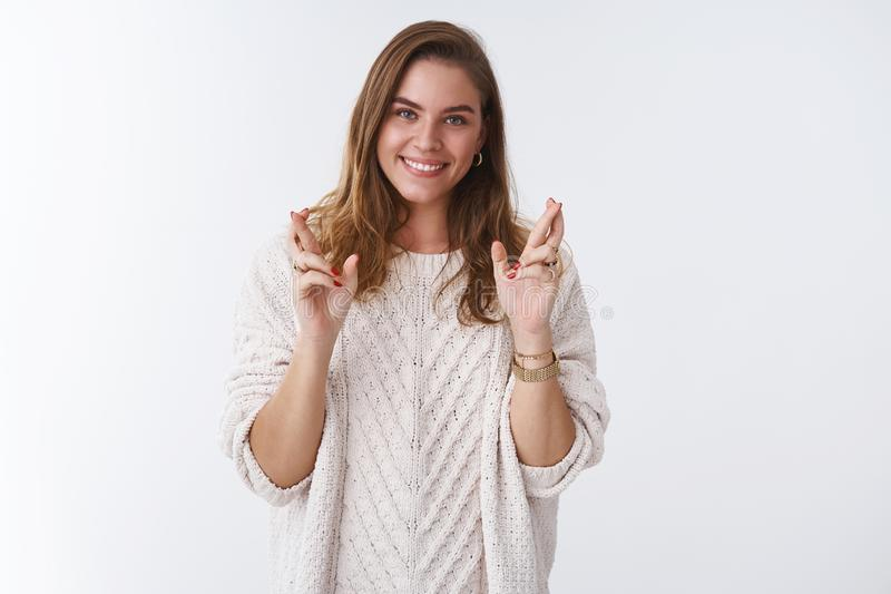 Hopeful optimistic charming young modern millenial european woman wearing loose stylish sweater cross fingers good luck royalty free stock images