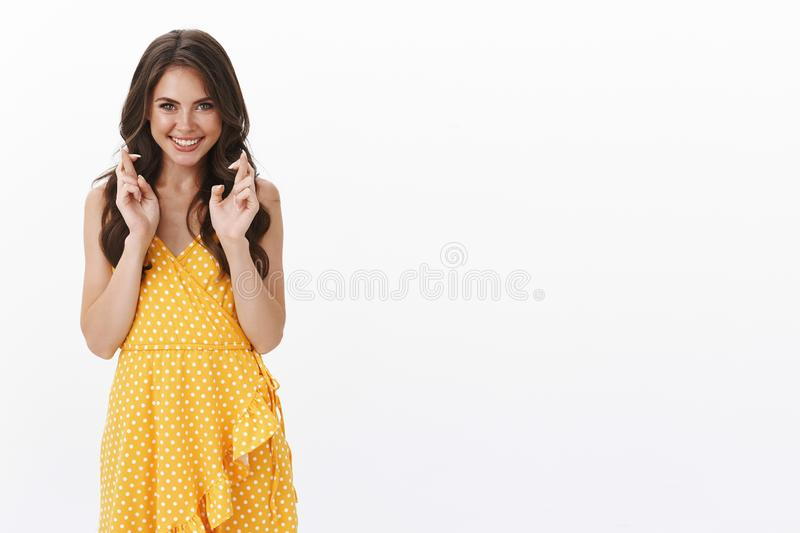 Hopeful optimistic lucky gorgeous glam woman in stylish yellow dress, smiling anticipating win, cross fingers good royalty free stock image