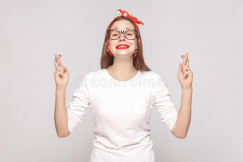 hopeful portrait of beautiful emotional young woman in white t-shirt with glasses, red lips and head band looking at camera with stock image