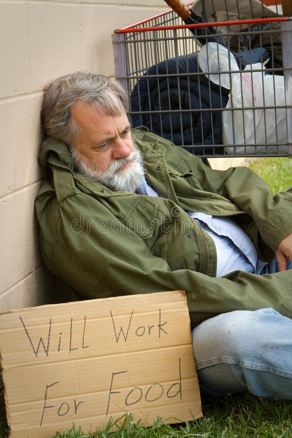 Hopeless Homeless. Homeless and hopeless man in an old army jacket waits for a handout royalty free stock image