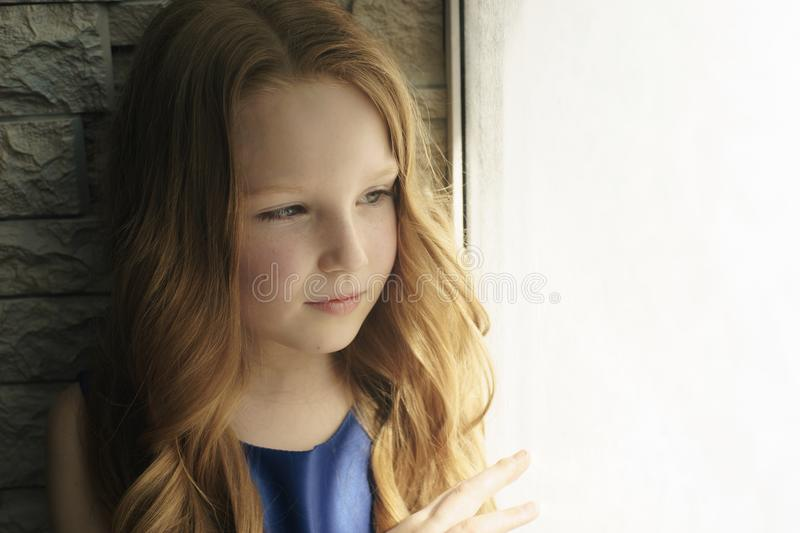 Hopeless life. Close up of depressed poor little girl standing near window and looking aside while feeling miserable. Hopeless life. Close up of depressed poor stock images