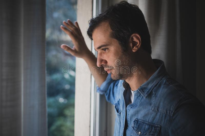 Hopeless man feeling alone and lost looking out window. Desperate man feeling sick and tired stock photos