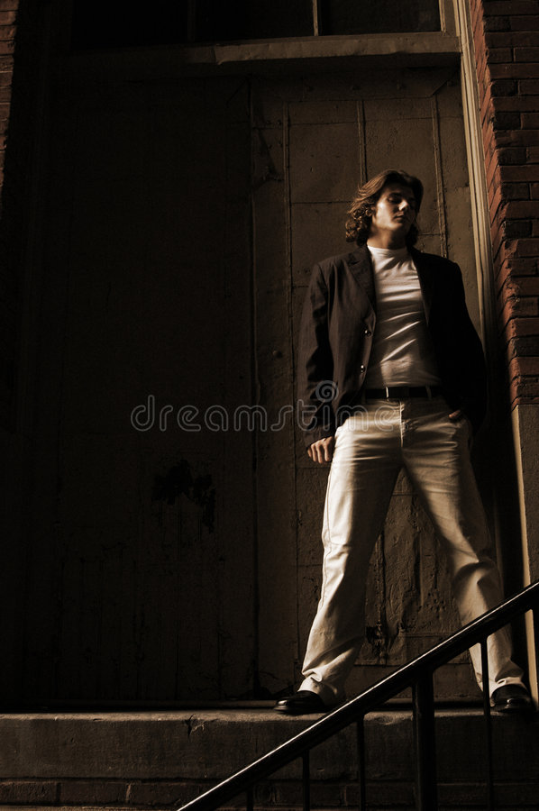 Hopeless romantic. Young male model with long hair in a gritty out door setting a whisper of light hits his body from the side there are dark areas in the image royalty free stock photos