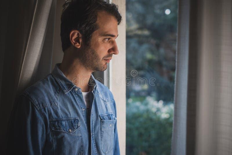 Hopeloos mensengevoel alleen en het verloren kijken uit venster royalty-vrije stock foto