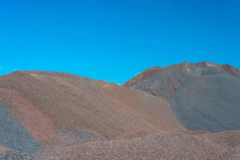 Hopen van grint en verpletterd op blauwe hemel bij een industriële cementinstallatie royalty-vrije stock afbeelding