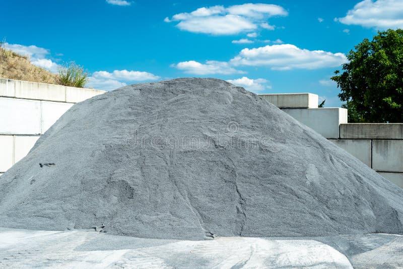 Hopen van grint en verpletterd op blauwe hemel bij een industriële cementinstallatie stock foto