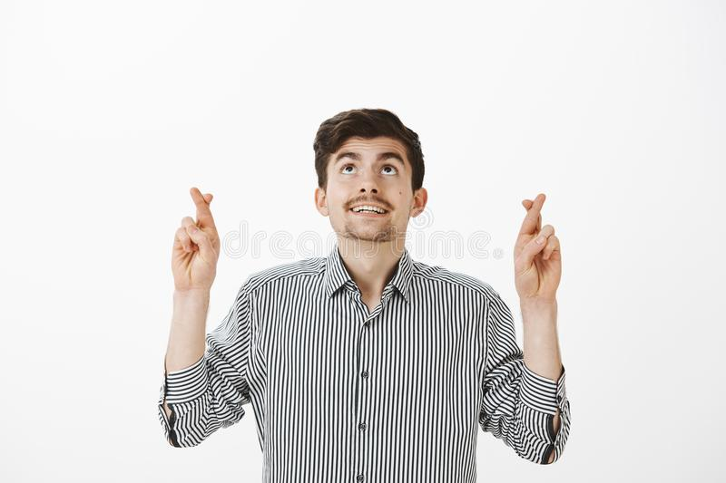 Hoping joyful attractive bearded guy in striped shirt, looking up while crossing fingers and making with or praying in royalty free stock photos