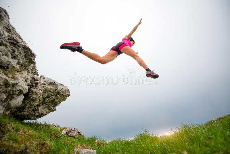 Hopp av en sportig kvinnaidrottsman nen som kör i bergen arkivfoto