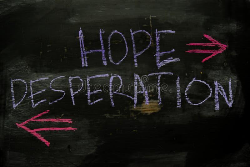 Hopp eller desperation som är skriftliga med färgkritabegrepp på svart tavla royaltyfria bilder