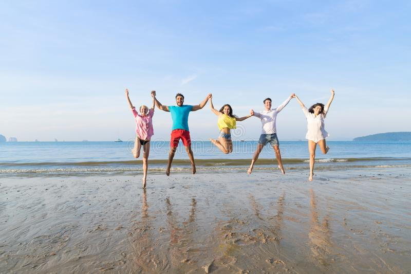 Hopp för ungdomargrupp på strandsommarsemestern, lyckligt le vänhav arkivbilder