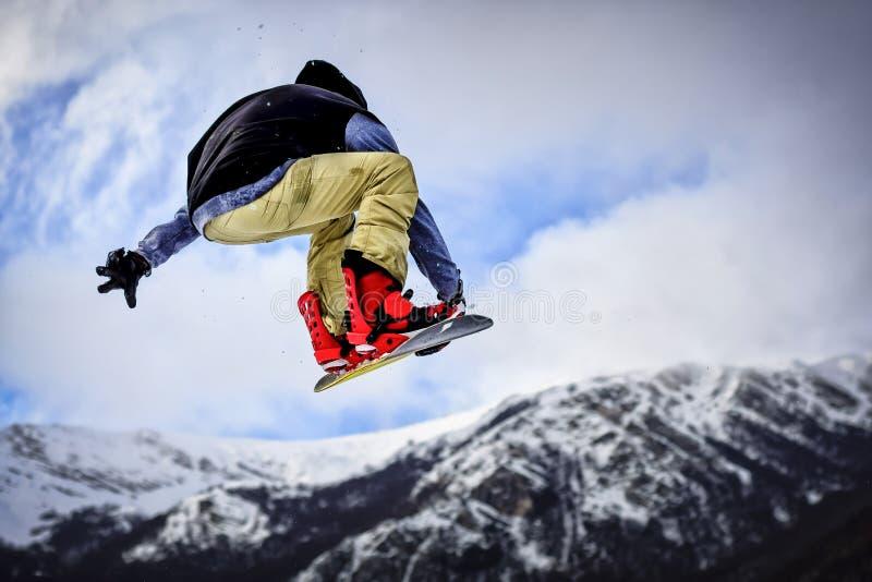 Hopp med snowboarden i Backcountry arkivfoto