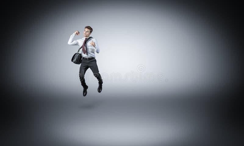 Hoppa affärsmannen på grå färger arkivbild