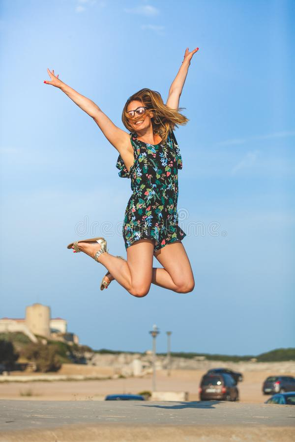 Hoppa av lycka Glat och le den unga kvinnan hoppar upp med lyftta armar royaltyfria foton