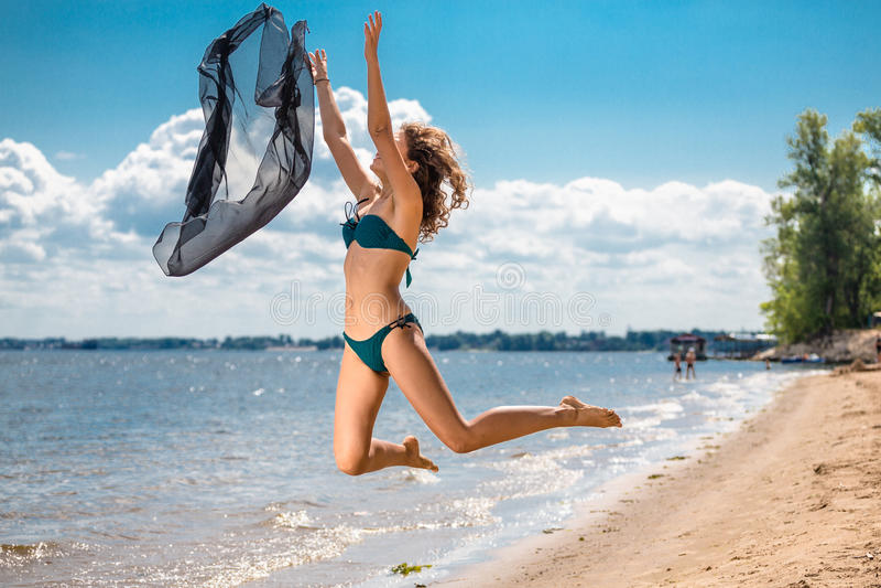Hoppa den lyckliga flickan på stranden, sportig sund sexig kropp för passform i bikini royaltyfri bild