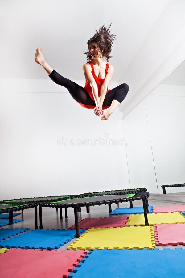 Hoppa den unga kvinnan på en trampolin arkivbild