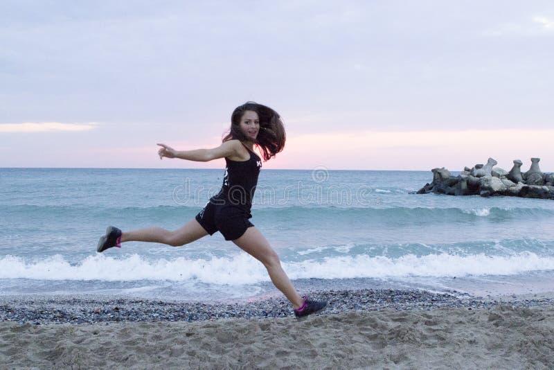 Hoppa för ung kvinna som är lyckligt på stranden som utarbetar royaltyfria bilder