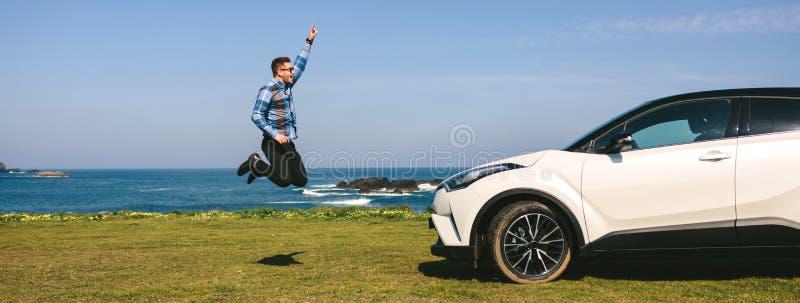 Hoppa för ung man som är lyckligt med bilen royaltyfri foto
