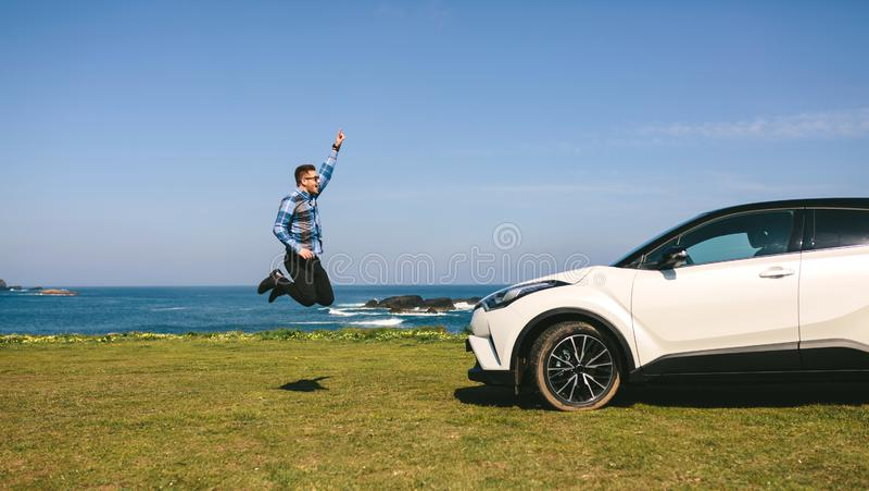 Hoppa f?r ung man som ?r lyckligt med bilen royaltyfri bild