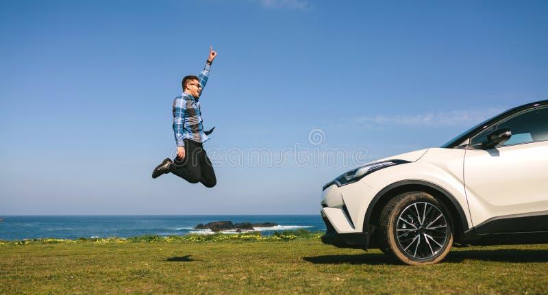 Hoppa f?r ung man som ?r lyckligt med bilen arkivbilder