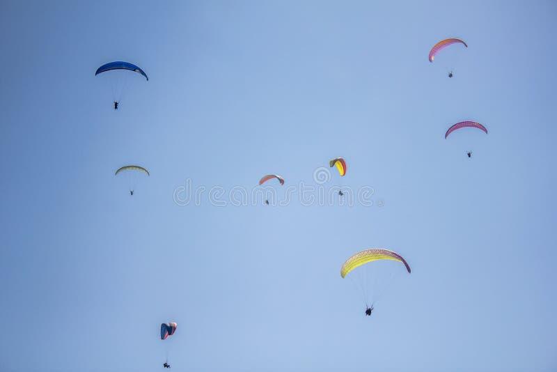 Hoppa fallskärm flera paragliders på färgrikt i en klar blå himmel royaltyfri fotografi