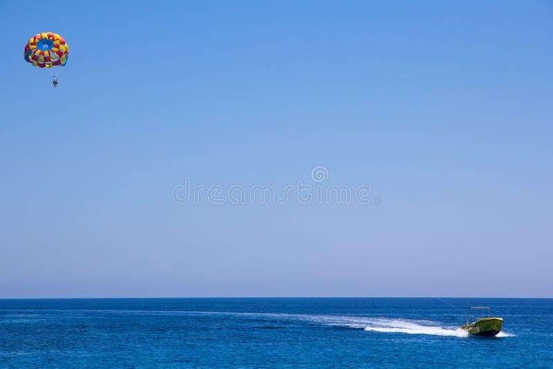 Hoppa fallskärm med folkflugan under det motoriska fartyget fotografering för bildbyråer
