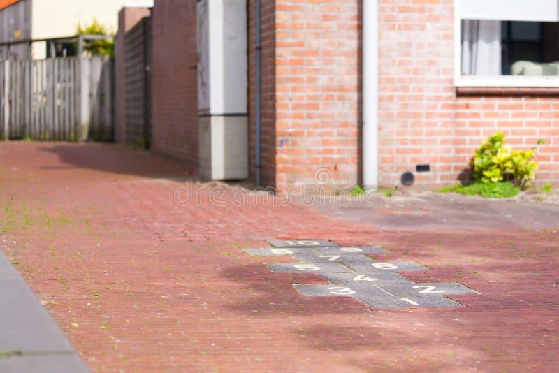 Hoppa hagebarns lek som dras med krita på trottoar, playgroun royaltyfri bild