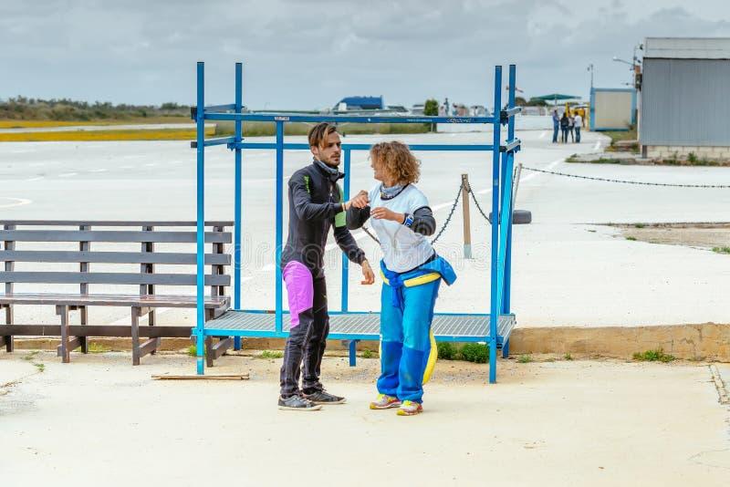 Hoppa med fritt fall instruktören undervisar henne den korrekta hoppa med fritt fall positionen, innan att hoppa arkivbild