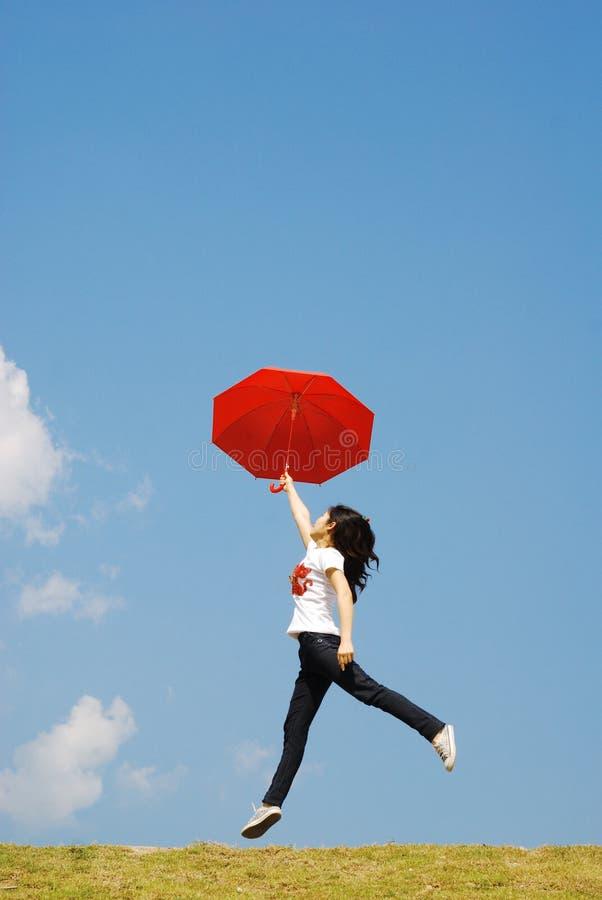 hoppa röd sky till paraplykvinnan royaltyfri bild