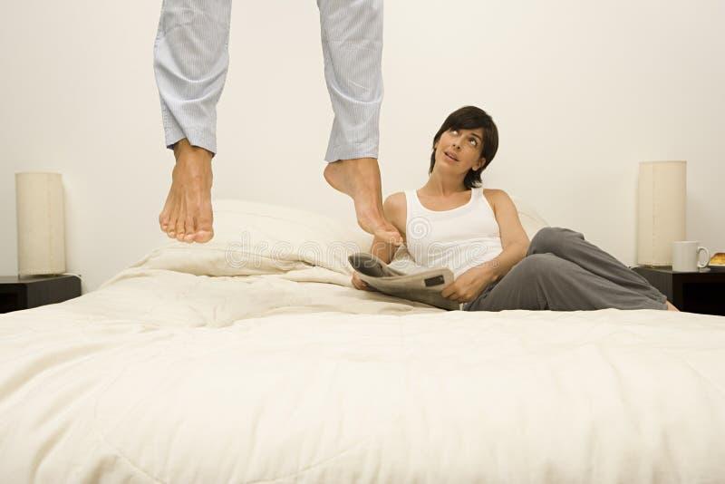 Hoppar den hållande ögonen på maken för kvinnan på säng royaltyfria bilder