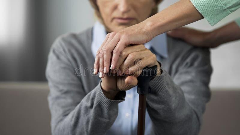 Hopplös kvinnlig pensionär som sitter på den unga sjuksköterskan för soffa som försiktigt trycker på hennes händer royaltyfri foto