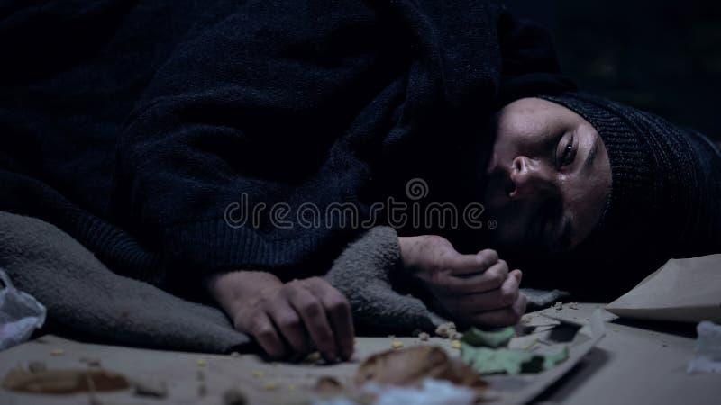 Hopplös luffare som mycket ligger på golv av avskräde, armod, social osäkerhet royaltyfri foto