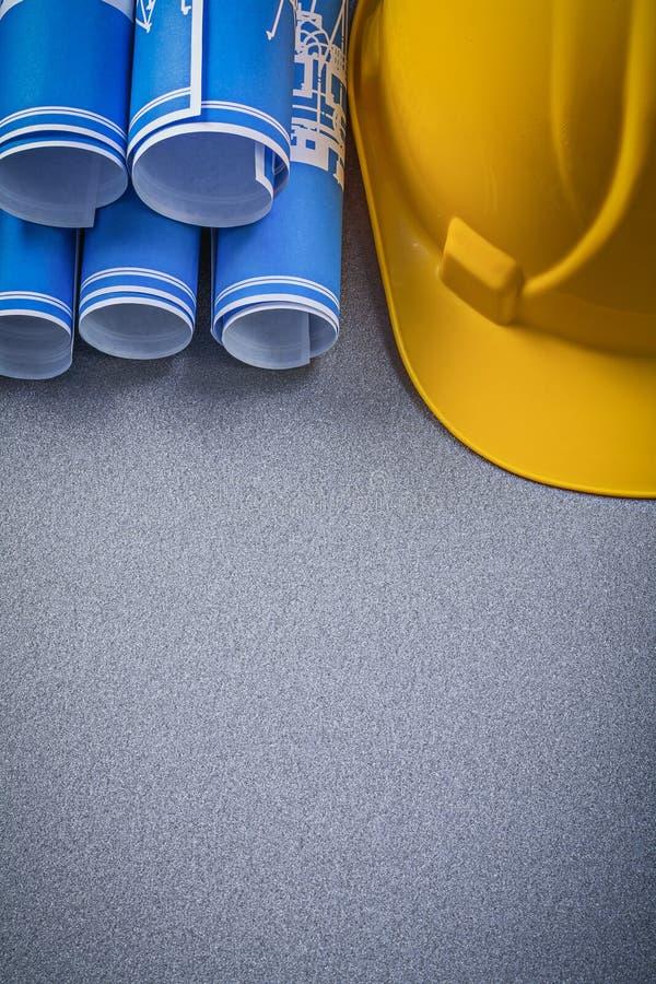 Hoprullade byggnadsritningar för byggnadshjälmblått på grå färgbac arkivbilder