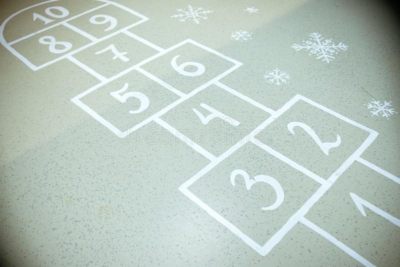 Hopscotch court with numbers from 1 to 10 drawn with white paint on the asphalt.Child playing hopscotch game.activities stock photos