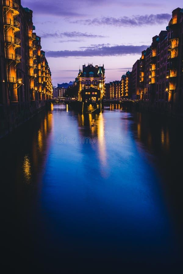 Hora azul en el distrito de Warehouse - Speicherstadt con la lila coloreó el cielo Señal Wandrahmsfleet del turismo en crepúsculo imagenes de archivo