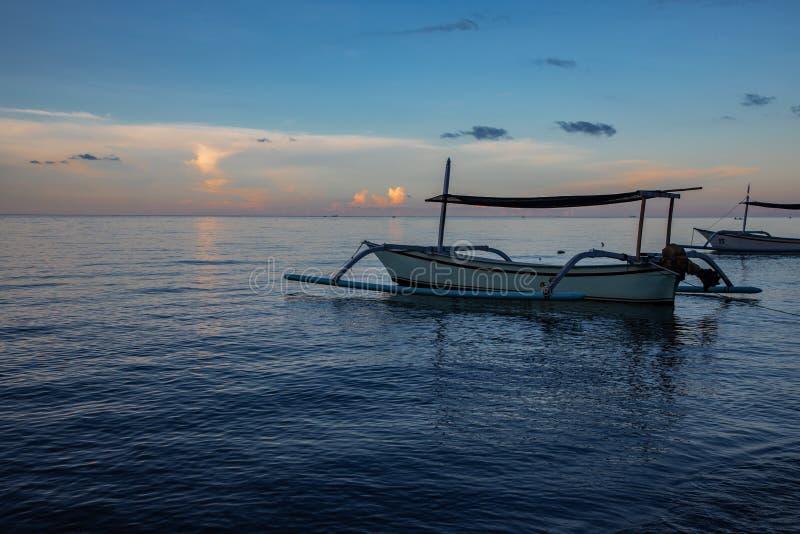 Hora azul sobre o oceano calmo e a praia preta da areia com barco do balinese foto de stock