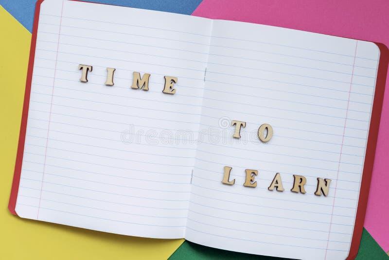 Hora de aprender, texto em um caderno aberto, folhas de papel coloridas o fotos de stock