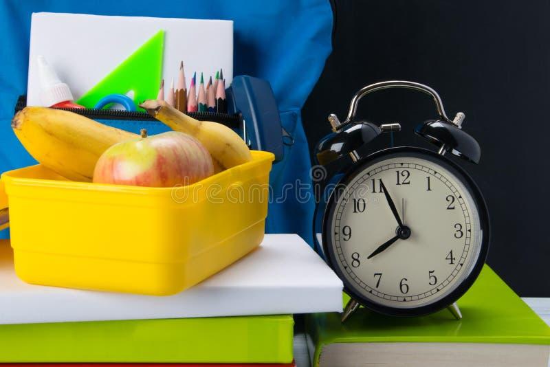 hora de comer do recipiente amarelo, entre lições, fundo com uma banana e uma maçã imagem de stock royalty free