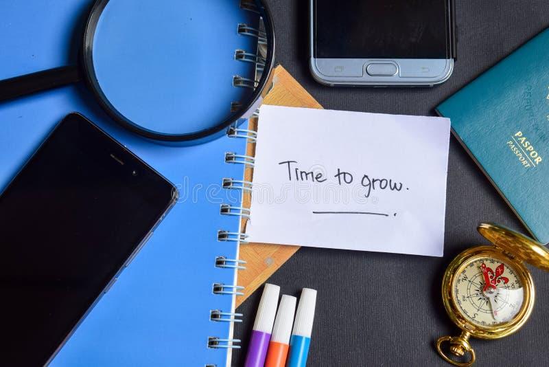 Hora de crescer escrito agora no papel passaporte, lupa, compasso, Smartphone fotos de stock