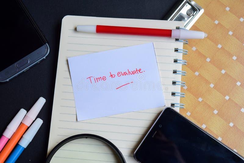 Hora de evaluar la palabra escrita en el papel Hora de evaluar el texto en el libro de trabajo, concepto del negocio de la tecnol fotos de archivo